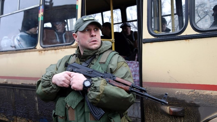 In this image taken Tuesday Feb. 3, 2015 a Ukrainian soldier holds a weapon as people wait on a bus to leave the town of Debaltseve  Ukraine, Tuesday, Feb. 3, 2015. Soldiers bark orders at exhausted residents boarding evacuation buses with overflowing bags in hand, as another rebel artillery attack pummels this town on the front lines of Ukraine's separatist war. Despair is deepening for a shrinking population that has been without power, heating and running water for almost two weeks. The relentless rebel advance on the  railway town of Debaltseve is being slowed only by Ukrainian tanks, cannons and rocket launchers.  (AP Photo/Petr David Josek)