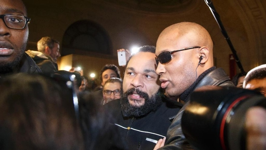"French comedian Dieudonne M'Bala M'Bala, center, leaves a Paris court house flanked by his body guards, Wednesday, Feb. 4, 2015. Controversial French comic Dieudonne has gone on trial charged with ""defending terrorism"" in a Facebook post made after the three-day terror spree in Paris last month. He made a Facebook posting which said ""I feel like Charlie Coulibaly."" The post, which has since been taken down, merges the names of Charlie Hebdo, the satirical magazine where two gunmen killed 12 people, and that of Amedy Coulibaly, who prosecutors say killed four hostages at a kosher supermarket and a policewoman. (AP Photo/Michel Euler)"