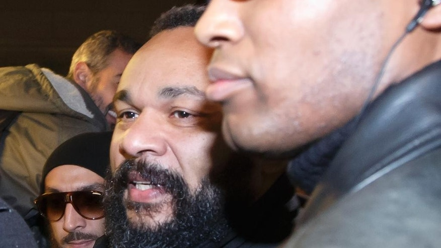 "French comedian Dieudonne M'Bala M'Bala leaves a Paris court house with his body guard, Wednesday, Feb. 4, 2015. Controversial French comic Dieudonne has gone on trial charged with ""defending terrorism"" in a Facebook post made after the three-day terror spree in Paris last month. He made a Facebook posting which said ""I feel like Charlie Coulibaly."" The post, which has since been taken down, merges the names of Charlie Hebdo, the satirical magazine where two gunmen killed 12 people, and that of Amedy Coulibaly, who prosecutors say killed four hostages at a kosher supermarket and a policewoman. (AP Photo/Michel Euler)"