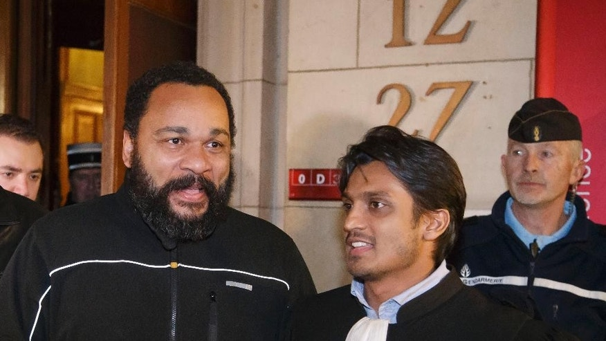 "French comedian Dieudonne M'Bala M'Bala, left, and his lawyer Sanjay Mirabeau, right, leave a Paris court house, Wednesday, Feb. 4, 2015. Controversial French comic Dieudonne has gone on trial charged with ""defending terrorism"" in a Facebook post made after the three-day terror spree in Paris last month. He made a Facebook posting which said ""I feel like Charlie Coulibaly."" The post, which has since been taken down, merges the names of Charlie Hebdo, the satirical magazine where two gunmen killed 12 people, and that of Amedy Coulibaly, who prosecutors say killed four hostages at a kosher supermarket and a policewoman. (AP Photo/Michel Euler)"