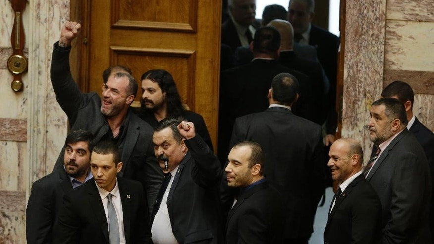 FILE -  In this file photo taken Monday, Dec. 29, 2014 lawmakers from the extreme right Golden Dawn party signal against the government, at the parliament in Athens. A judicial panel in Athens on Wednesday, Feb. 4, 2015 has ruled that the leader and lawmakers from the extreme right Golden Dawn party will stand trial on criminal charges of participating in a criminal group — an offence that carries a 20-year prison sentence. (AP Photo/Thanassis Stavrakis, File)