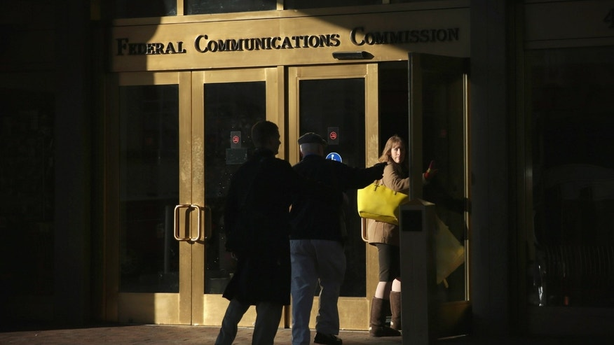 WASHINGTON, DC - DECEMBER 11:  People enter the Federal Communications Commission building December 11, 2014 in Washington, DC. The commission held its monthly meeting as activists held a rally outside to call for net neutrality.  (Photo by Alex Wong/Getty Images)