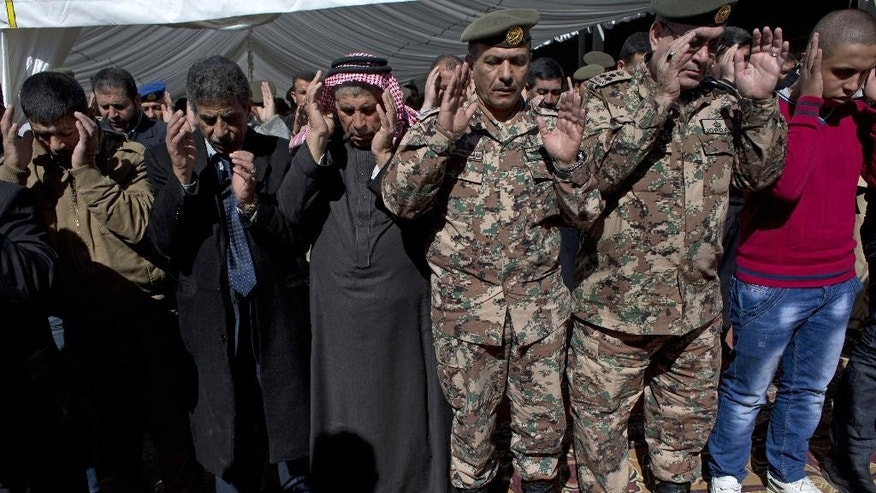 Safi al-Kaseasbeh, third left, father of slain Jordanian pilot, Lt. Muath al-Kaseasbeh prays during a mass funeral at the Kaseasbeh tribe's gathering divan at their home village of Ai, near Karak, Jordan, Wednesday, Feb. 4, 2015. Outrage and condemnation poured across the Middle East on Wednesday as horrified people learned of the video purportedly showing the Islamic State group burn a Jordanian pilot to death. (AP Photo/Nasser Nasser)