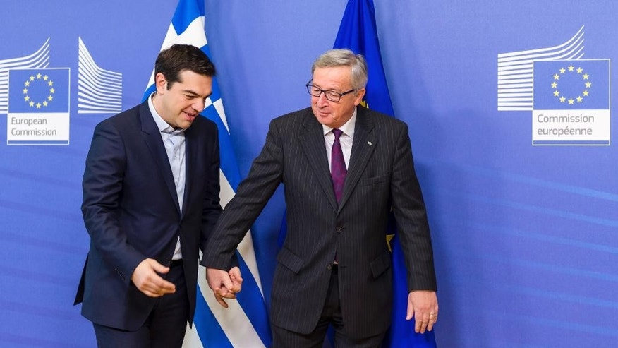 European Commission President Jean-Claude Juncker, right, walks hand in hand with Greece's Prime Minister Alexis Tsipras upon his arrival at the European Commission headquarters in Brussels Wednesday, Feb. 4, 2015. Tsiparis is on a one day trip to Brussels to meet with EU leaders. (AP Photo/Geert Vanden Wijngaert)