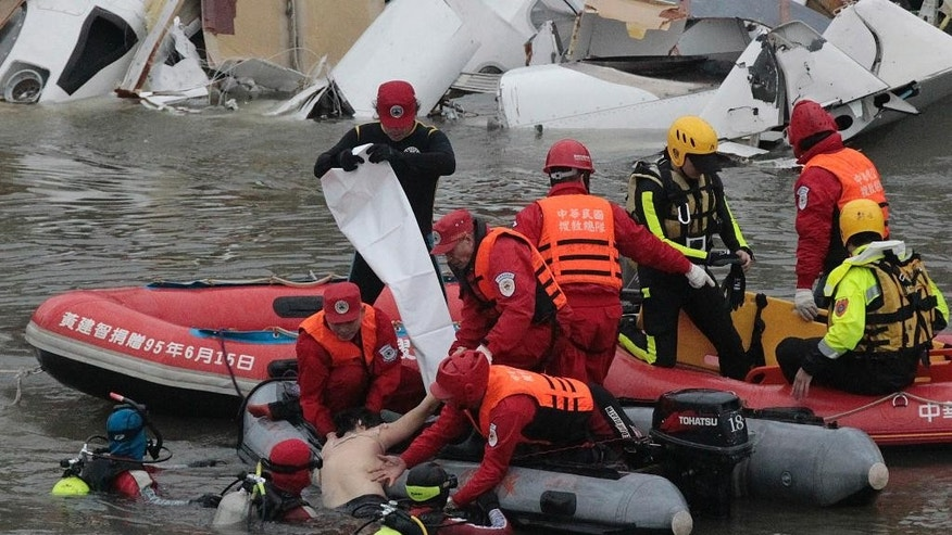 Emergency personnel retrieve the body of a passenger of a commercial plane after it crashed in the water in Taipei, Taiwan Wednesday, Feb. 4, 2015. The Taiwanese commercial flight with 58 people aboard clipped a bridge shortly after takeoff and crashed into the river in the island's capital on Wednesday morning. (AP Photo/Wally Santana)