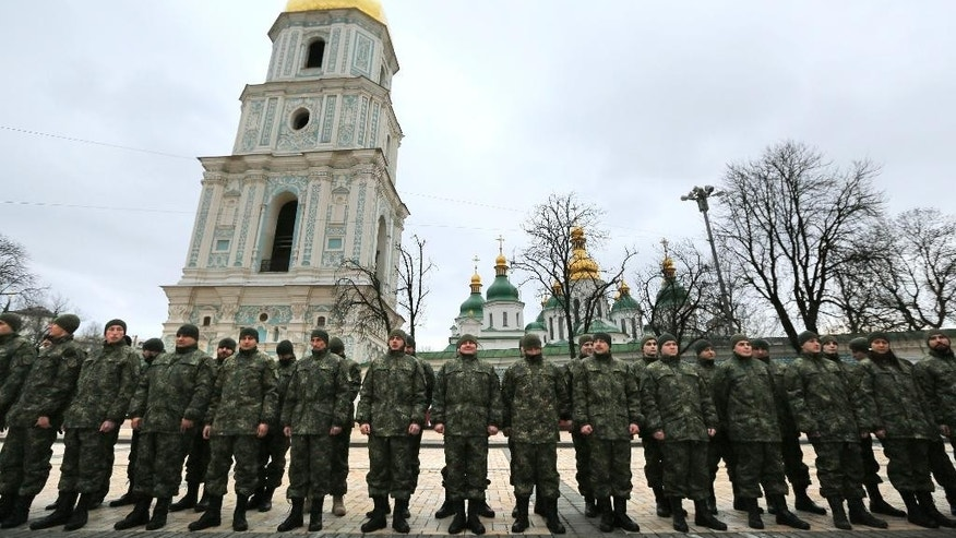 "Volunteers of the battalion ""St. Maria"" line up during a ceremony before military training in Internal Ministry unit at the Sophia Square near the St. Sophia Cathedral in Kiev, Ukraine,Tuesday, Feb. 3, 2015. (AP Photo/Sergei Chuzavkov)"