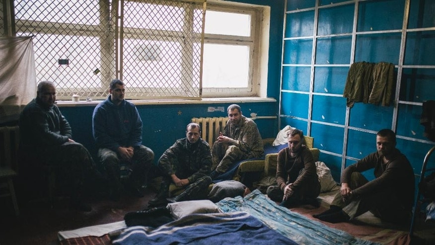 Ukrainian Army soldiers  being held as prisoners sit in a hall inside a Russian-backed separatist military base outside Donetsk, Ukraine, Tuesday, Feb. 3, 2015. Since the unrest in eastern Ukraine surged anew in early January, the separatists have made notable strides in clawing territory away from the government in Kiev. Their main offensive is now directed at Debaltseve — a government-held railway junction once populated by 25,000 people that lies between the rebel-held cities of Luhansk and Donetsk. Almost 2,000 residents have fled in the last few days alone.  (AP Photo/Vadim Braydov)