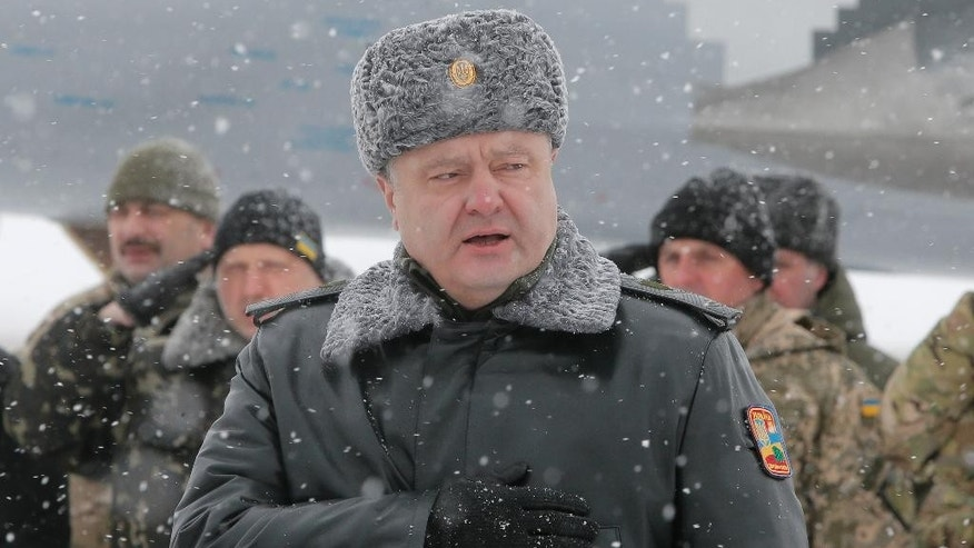 In this photo taken Jan. 5, 2015, Ukrainian president Petro Poroshenko sings a Ukrainian national anthem during a ceremony for the delivery of more than 100 pieces military equipment to the Ukrainian armed forces, near  city of Zhitomir, Ukraine. Ukrainian President Petro Poroshenko said late Tuesday that he is confident that the United States will send weapons to his country to help it fight pro-Russian rebels, a step the Americans reportedly are considering. (AP Photo/Efrem Lukatsky)