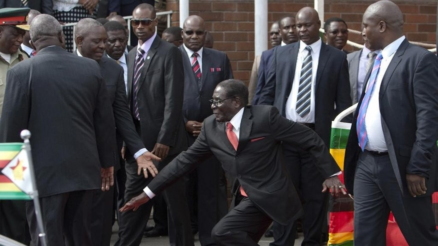 Feb. 4, 2015: Zimbabwean President Robert Mugabe, center, falls after addressing supporters upon his return from an African Union meeting in Ethiopia. (AP)