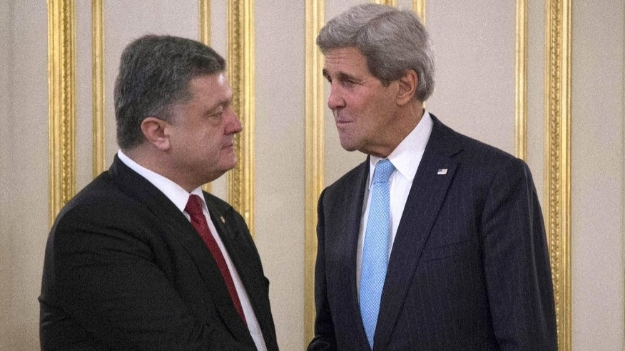 Ukrainian President Petro Poroshenko, left, shakes hands with U.S. Secretary of State John Kerry during a meeting in Kiev, Ukraine, Thursday, Feb. 5, 2015. The Ukrainian government is anxious to use Thursday's visit by U.S. Secretary of State John Kerry to Kiev to reiterate its plea for lethal aid. President Barack Obama has opposed the idea of sending weapons to Ukraine but sources in his administration say this position could change in the light of recent events. (AP Photo/Jim Watson, Pool)
