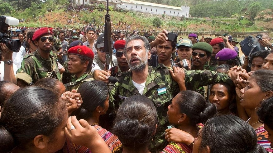 In this Oct. 24, 1999, photo, then East Timorese rebel leader Xanana Gusmao is embraced as he returns to the Armed Forces of National Liberation of East Timor (FALINTIL) rebel army camp for the first time since his release from an Indonesian prison, in Remexio, in the hills outside of Dili, East Timor. East Timor independence hero Prime Minister Xanana Gusmao resigned as prime minister Friday, Feb. 6, 2015, stepping down ahead of an expected restructuring of the government next week. (AP Photo/Charles Dharapak)
