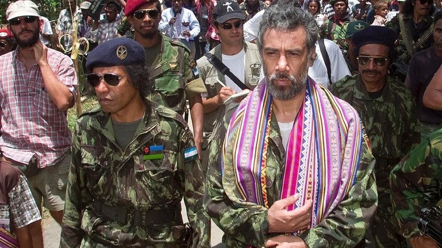 In this Oct. 24, 1999, photo, then East Timorese rebel leader Xanana Gusmao, right, walks with Taur Matan Ruak, left, then commander of the Armed Forces of National Liberation of East Timor (FALINTIL) as he returns to the rebel army camp for the first time since his imprisonment by Indonesia, in Remexio, in the hills outside of Dili, East Timor. East Timor independence hero Prime Minister Xanana Gusmao resigned as prime minister Friday, Feb. 6, 2015, stepping down ahead of an expected restructuring of the government next week. (AP Photo/Charles Dharapak)