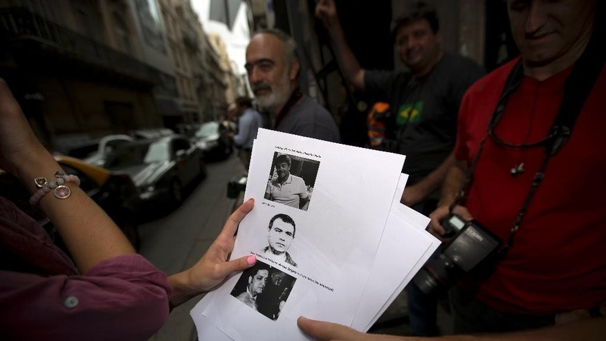 Reporters and photojournalists look at a printout with photos that identify for them potential witnesses that might be be called in to the prosecutor's office that leads the investigation of prosecutor Alberto Nisman's death, Buenos Aires, Argentian, Thursday, Feb. 5, 2015. Investigators examining the death of Nisman who accused President Fernandez of agreeing to shield the alleged masterminds of a 1994 terror bombing said Tuesday they found a draft document he wrote requesting her arrest. (AP Photo/Rodrigo Abd)