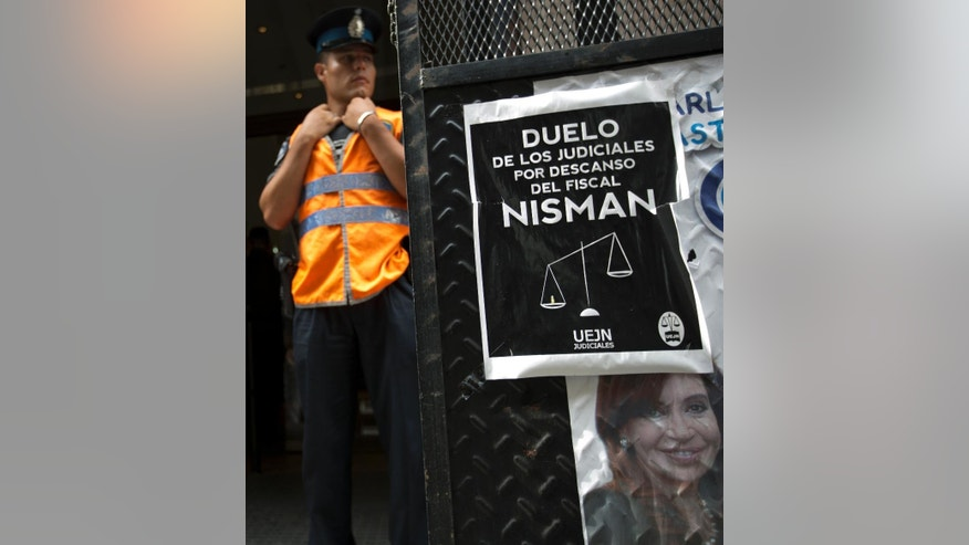 "A police officer stands guard in front of he prosecutor's office that leads the investigation of prosecutor Alberto Nisman's death, in Buenos Aires, Argentina, Thursday, Feb. 5, 2015. Posted on the gate is a portrait of Argentina's President Cristina Fernandez along with another poster that reads in Spanish ""Mourning of judicial workers due to the death of prosecutor Nisman."" Investigators examining the death of Nisman who accused President Fernandez of agreeing to shield the alleged masterminds of a 1994 terror bombing said Tuesday they found a draft document he wrote requesting her arrest. (AP Photo/Rodrigo Abd)"