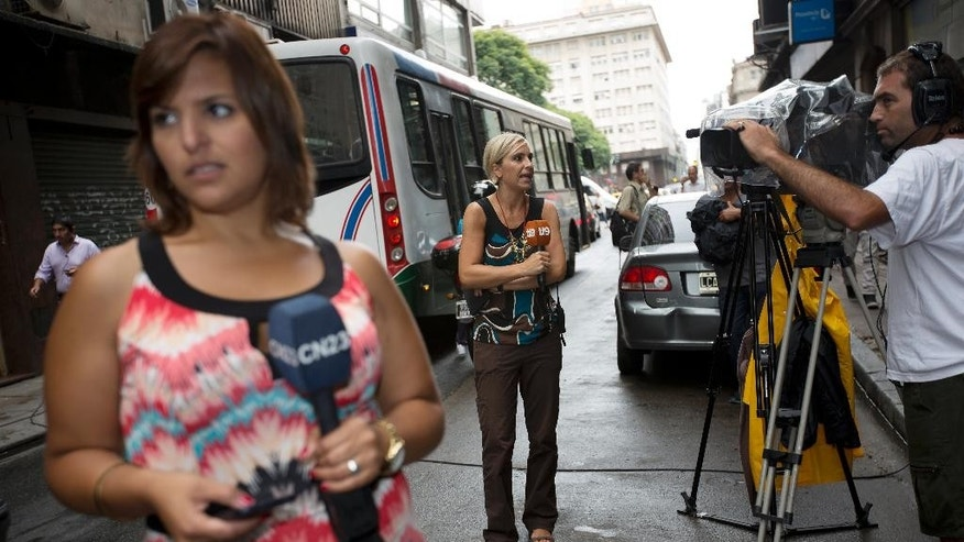 Television journalists file their reports from street in front of the prosecutor's office that leads the investigation of prosecutor Alberto Nisman's death, Buenos Aires, Argentina, Thursday, Feb. 5, 2015. Investigators examining the death of Nisman who accused President Fernandez of agreeing to shield the alleged masterminds of a 1994 terror bombing said Tuesday they found a draft document he wrote requesting her arrest. (AP Photo/Rodrigo Abd)