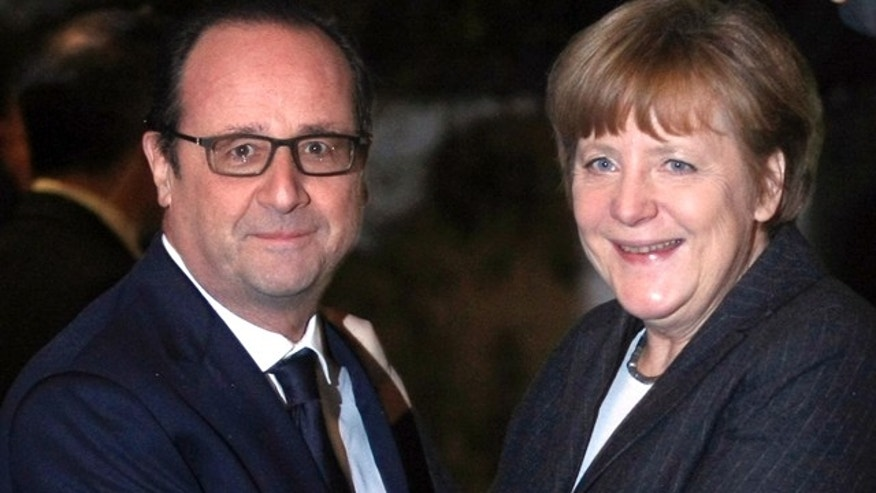 Jan. 30, 2015: French President Francois Hollande, left, greets German Chancellor Angela Merkel, prior to their informal dinner at the restaurant, Zum Ysehuet, in Strasbourg, France. (AP Photo/Christian Lutz, Pool)