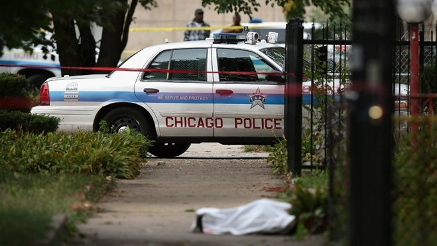 Police investigate the shooting death of 14-year-old Tommy McNeal, whose body is covered by a sheet on the sidewalk on September 20, 2013 in Chicago, Illinois. (Photo by Scott Olson/Getty Images)