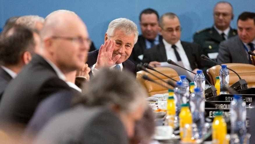 U.S. Secretary of Defense Chuck Hagel, center, waves across the table as he waits for the start of the NATO-Georgia Commission at the level of defense ministers at NATO headquarters in Brussels on Thursday, Feb. 5, 2015. NATO defense ministers meet Thursday to discuss terrorism, the situation in Ukraine and the size and composition of the new spearhead force. (AP Photo/Virginia Mayo)