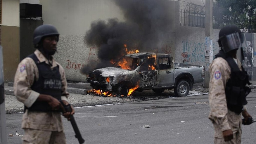 Flames rise from a truck after it was set on fire by protesters demanding the government lower fuel prices, in Port-au-Prince, Haiti, Thursday, Feb. 5, 2015. Demonstrators are promising to disrupt the upcoming national carnival if the costs don't go down. (AP Photo/Dieu Nalio Chery)