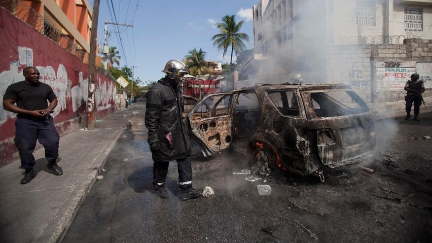A firefighter walks next to the charred shell of car after it was set on fire by protesters demanding the government lower fuel prices, in Port-au-Prince, Haiti, Thursday, Feb. 5, 2015. Demonstrators are promising to disrupt the upcoming national carnival if the costs don't go down. (AP Photo/Dieu Nalio Chery)