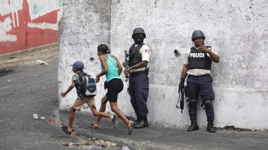 A woman and child run past police officers responding to protesters demanding the government lower fuel prices, in Port-au-Prince, Haiti, Thursday, Feb. 5, 2015. Protesters burned tires and threw rocks, while police officers responded with tear gas. Demonstrators are promising to disrupt the upcoming national carnival if the costs don't go down. (AP Photo/Dieu Nalio Chery)