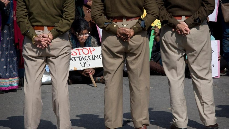 Indian policemen stand guard as Christians hold placards protesting against recent attacks on churches in the Indian capital outside the Sacred Heart Church in New Delhi, India, Thursday, Feb. 5, 2015. Police said the protesters were detained as they marched toward the residence of Home Minister Rajnath Singh in a high-security area where protests are banned. On Monday, a church was vandalized in New Delhi when unidentified people broke in and desecrated holy objects kept in the church, the fifth such attack on a Christian church since December. (AP Photo /Manish Swarup)