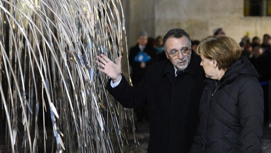 President of the Federation of Jewish Religious Communities of Hungary (Mazsihisz) Andras Heisler  left, shows the Tree of Life memorial to German Chancellor Angela Merkel in the garden of Dohany Street Synagogue in Budapest, Hungary, Monday, Feb. 2, 2015. Merkel is staying in Hungary on a one-day official visit. (AP Photo/MTI, Tamas Kovacs)
