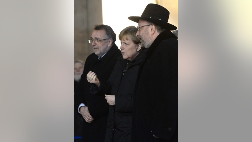 German Chancellor Angela Merkel, center, is flanked by Chief Rabbi of the Synagogue Robert Froelich, right, and President of the Federation of Jewish Religious Communities of Hungary (Mazsihisz) Andras Heisler , left, in the garden of Dohany Street Synagogue in Budapest, Hungary, Monday, Feb. 2, 2015. Merkel is staying in Hungary on a one-day official visit. (AP Photo/MTI, Tamas Kovacs)