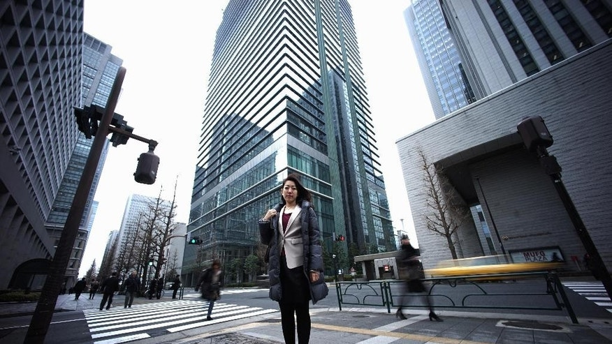 "In this Jan. 21, 2015 photo, 36-year-old Eriko Sekiguchi stands at a crossroad of business district in Tokyo. Often toiling 14 hours a day for a major trading company, including early morning meetings and after-hours ""settai,"" or networking with clients, she used just eight of her 20 paid vacation days last year. Six of those days were for being sick. (AP Photo/Eugene Hoshiko)"