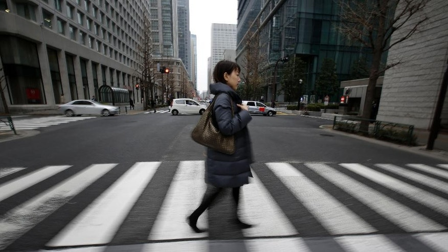 "In this Jan. 21, 2015 photo, 36-year-old Eriko Sekiguchi walks at a crossroad of business district in Tokyo. Often toiling 14 hours a day for a major trading company, including early morning meetings and after-hours ""settai,"" or networking with clients, she used just eight of her 20 paid vacation days last year. Six of those days were for being sick. (AP Photo/Eugene Hoshiko)"