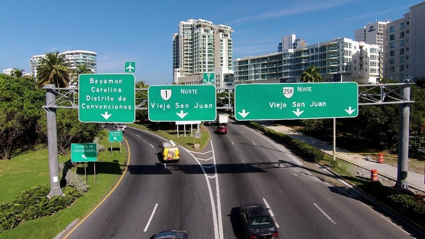 In this Jan. 28, 2015 photo, street signs provide directions to Old San Juan, Puerto Rico. Several hundred wealthy U.S. citizens have taken up residence in Puerto Rico, lured by incentives that allow them to pay minimal taxes on investment income in what critics say is a misguided effort to reverse a decade of economic decline that has prompted a middle-class exodus. (AP Photo/Ricardo Arduengo)