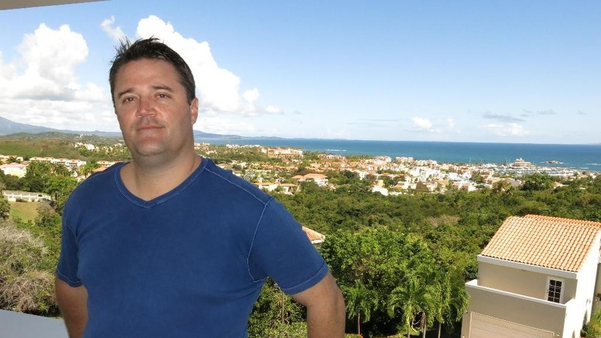 In this Jan. 30, 2015 photo, bond trader Ben Eiler poses for a photo on the second-floor balcony of his new home in Humacao, Puerto Rico. The towering 38-year-old native of Arkansas is one of at least 250 people who've accepted Puerto Rico's invitation to well-heeled U.S. citizens to move to the island and enjoy life without taxes on capital gains, an enticing offer for those whose income is derived from investments. (AP Photo/Danica Coto)