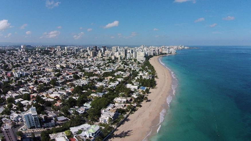 This Jan. 28, 2015 photo shows an aerial view of beachfront houses in the exclusive neighborhood of Ocean Park in San Juan, Puerto Rico. Lawyers and tax experts in Puerto Rico say they get calls daily from people seeking to take advantage of the Commonwealth's tax incentives, including managers of hedge funds or private equity funds who make most of their money from capital gains. (AP Photo/Ricardo Arduengo)