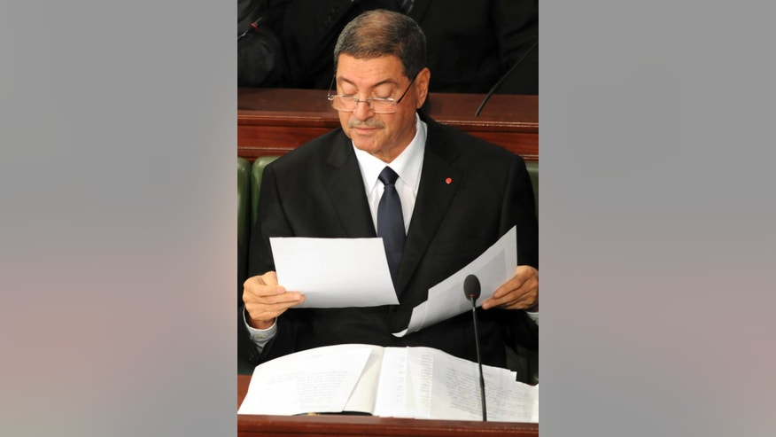Tunisian Prime Minister Habib Essid checks documents before delivering his speech at the national assembly in Tunis, Wednesday, Feb.4, 2015. The government faces a confidence vote in parliament on Wednesday, which it is expected to pass. The new government faces a battle against high inflation and high unemployment. (AP Photo/Hassene Dridi)