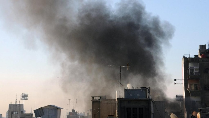 In this photo released by the Syrian official news agency SANA, smoke rises after rebels fired rockets and mortar shells that struck several parts in the capital Damascus, in Damascus, Syria, Thursday, Feb. 5, 2015. Syrian rebels fired a barrage of rockets and mortar shells that struck several neighborhoods in the capital Damascus on Thursday, killing many people and wounding tens, Syria's state-run news agency said. (AP Photo/SANA)