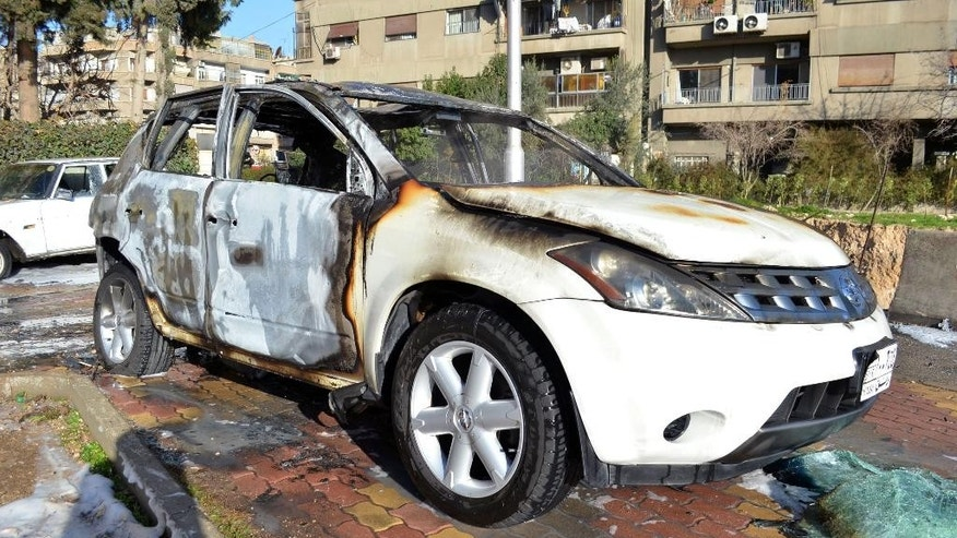 This photo released by the Syrian official news agency SANA, shows cars that were burned after rebels fired rockets and mortar shells that attack several parts in the capital Damascus, Syria, Thursday, Feb. 5, 2015. Syrian rebels fired a barrage of rockets and mortar shells that struck several neighborhoods in the capital Damascus on Thursday, killing many people and wounding tens, Syria's state-run news agency said. (AP Photo/SANA)