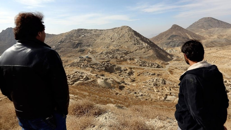 In this Sunday, Jan. 18, 2015 photo, Abdul Qadir Timor, director of archaeology at the Ministry of Information and Culture, left, looks at the view of Mes Aynak valley, some 40 kilometers (25 miles) southwest of Kabul, Afghanistan. The hills overlooking this ancient trade-route city, where the buried treasures of Afghanistan's Buddhist history hide beneath sandy soil, are so rich in copper that they gleam green in the morning sun. (AP Photo/Rahmat Gul)