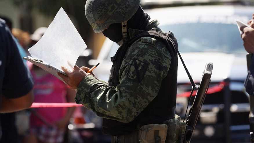 ACAPULCO, MEXICO - MARCH 02:  A Mexican army soldier takes notes at the site of a suspected drug-related double execution on March 2, 2012 in Acapulco, Mexico. Drug violence has surged in the coastal resort in the last year, making Acapulco the second most deadly city in Mexico after Juarez. One of Mexico's top tourist destinations, Acapulco has suffered a drop in business, especially from foreign tourists, due to the violence. Toursim accounts for about 70 percent of the economy of Acapulco's state of Guerrero and 9 percent of Mexico's economy.  (Photo by John Moore/Getty Images)