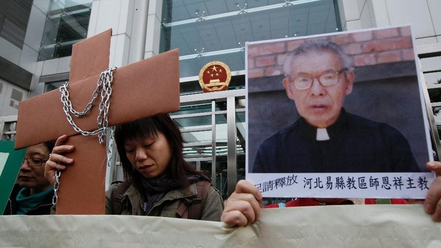 FILE - In this Tuesday, Dec. 7, 2010, file photo, protesters from the Justice & Peace Commission of The Hong Kong Catholic Diocese hold a picture of detained Bishop Shi Enxiang and a paper Cross during a demonstration outside the Chinese government liaison office in Hong Kong. On Friday, Feb. 6, 2015, a Roman Catholic website posted that Shi, who was detained in China for the past 14 years due to the country's feud with the Vatican, has died at age 94.(AP Photo/Kin Cheung, File)
