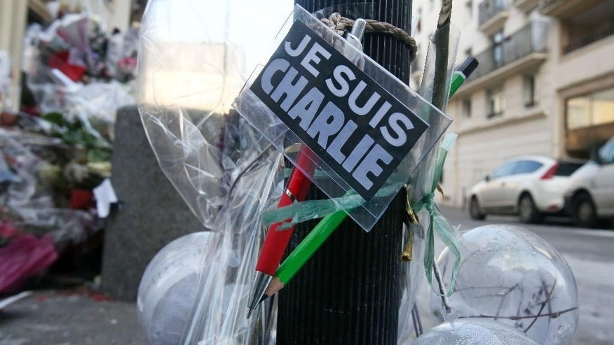 Flowers are laid near the headquarters of magazine Charlie Hebdo in Paris, Friday Feb. 6, 2015. Brothers Said and Cherif Kouachi killed 12 people in a terror attack at the offices of French satirical publication Charlie Hebdo on Jan. 7. The two gunmen, were killed by French police two days later. (AP Photo/Remy de la Mauviniere)