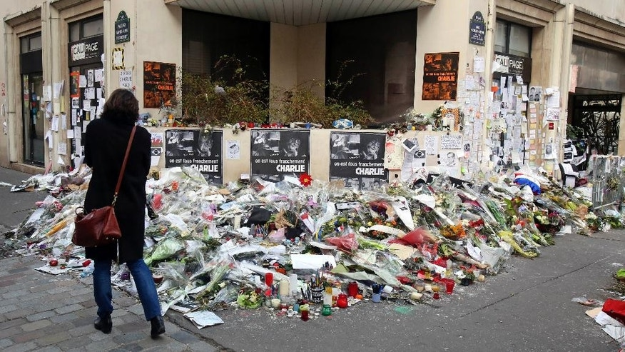 A woman looks at flowers laid near the headquarters of magazine Charlie Hebdo in Paris, Friday Feb. 6, 2015. Brothers Said and Cherif Kouachi killed 12 people in a terror attack at the offices of French satirical publication Charlie Hebdo on Jan. 7. The two gunmen, were killed by French police two days later. (AP Photo/Remy de la Mauviniere)