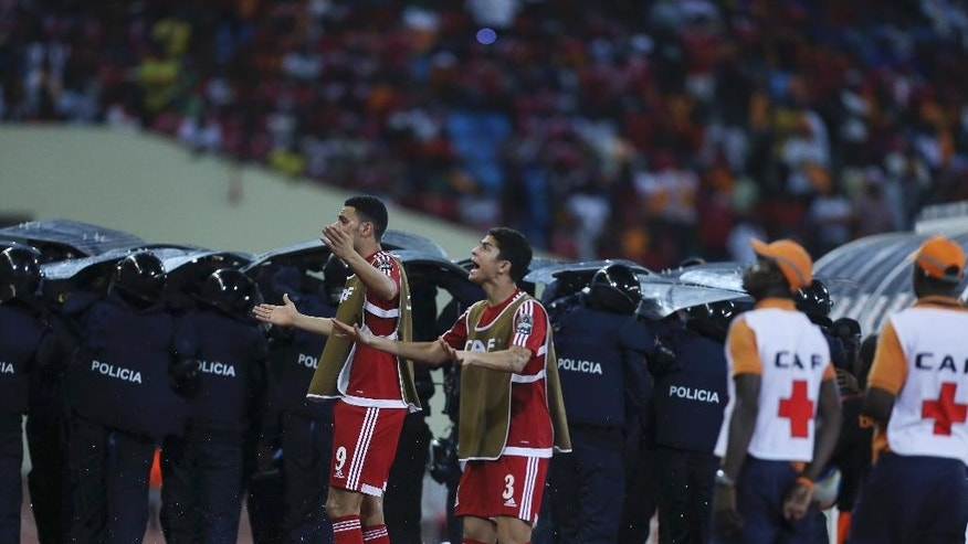 Police shield themselves as Equatorial Guinea's Raul Fabian Bosio, left, and Igor Engonga Noval, appeal to supporters to stop throwing object onto the pitch during their African Cup of Nations Semifinals soccer match with Ghana at Estadio De Malabo, Equatorial Guinea, Thursday Feb. 5, 2015. (AP Photo/Sunday Alamba)
