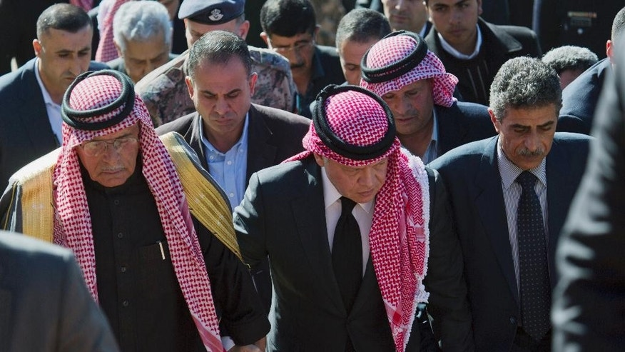 "Jordanian King Abdullah II, center, escorted by Safi al-Kaseasbeh, left, father of slain Jordanian pilot, Lt. Muath al-Kaseasbeh, and his uncle Fahed al-Kaseasbeh, arrives to offer his condolences at the memorial tent set up for the pilot at their home village of Ai, near Karak, Jordan, Thursday, Feb. 5, 2015. Jordan's king vowed to wage a ""harsh"" war against the Islamic State group after the militants burned a captive Jordanian pilot in a cage and released a video of the killing. (AP Photo/Nasser Nasser)"