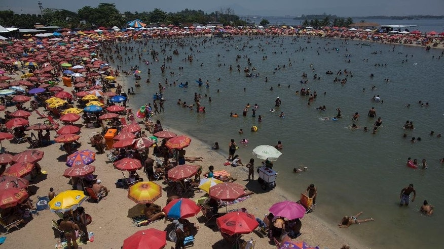 "In this Jan. 18, 2015 photo, people gather at the artificial beach Piscinao de Ramos or the ""Big Pool of Ramos"" in Rio de Janeiro, Brazil. An arguably unprecedented wave of robberies in recent weeks are taking place a year and a half before Rio plays host to the 2016 summer Olympics. People are seeking alternatives for their beach time because of the mass robberies known in Portuguese as ""arrastoes,"" or ""dragnets.""  In the attacks, groups of youth run through a beach crowd, sparking panic and grabbing cell phones, necklaces and other valuables as sun bathers run willy-nilly. (AP Photo/Leo Correa)"