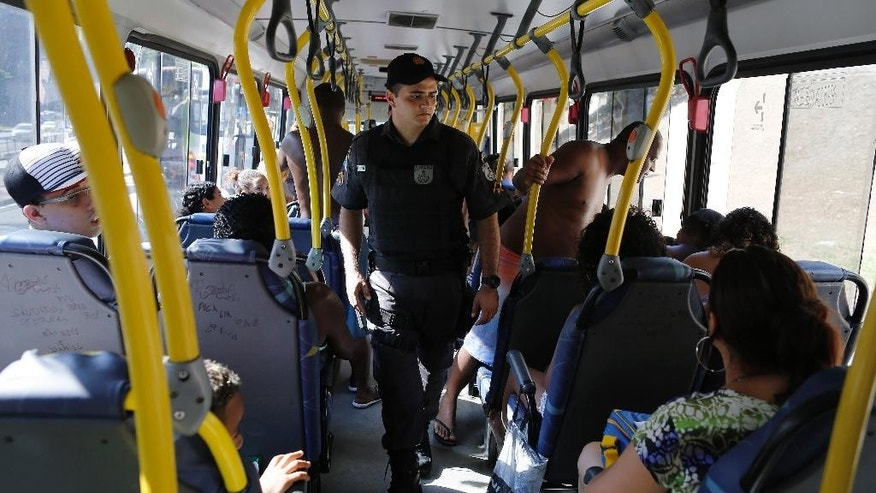In this Jan. 20, 2015 photo, a police officer checks a bus before it goes to the beaches in Rio de Janeiro, Brazil. Rio police are struggling to restore a sense of security to Ipanema, Arpoador and Copacabana beaches, which have been thronged by tens of thousands of bathers every weekend during a mid-summer heat wave. (AP Photo/Leo Correa)