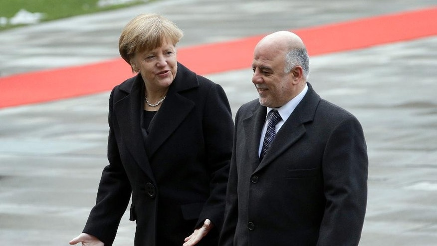 German Chancellor Angela Merkel, left, and the Prime Minister of Iraq, Haider al-Abadi, right, talk during a military welcome ceremony at the chancellery in Berlin, Germany, Friday, Feb. 6, 2015. (AP Photo/Michael Sohn)