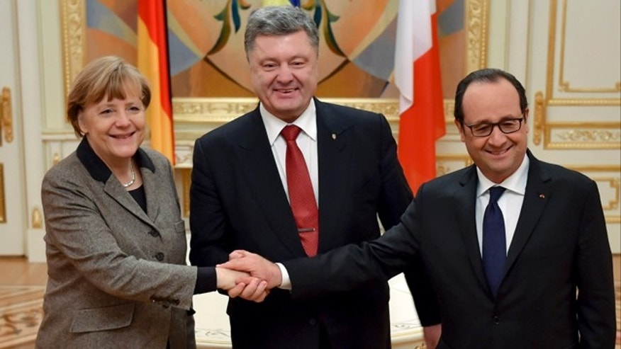 Feb 5, 2015: Ukrainian President Petro Poroshenko, center, French President Francois Hollande, right, and German Chancellor Angela Merkel shake hands during their meeting in Kiev. (AP Photo/Presidential Press Service, Mykola Lazarenko)
