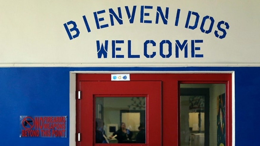 File - In this July 31, 2014 file photo, a Spanish and English welcome sign is seen above a door in a secured entrance area at the Karnes County Residential Center in Karnes City, Texas, one of two family detention centers that are applying for residential child care licenses. (AP Photo/Eric Gay, File)