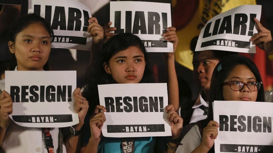 Protesters display their messages during a rally near the Presidential Palace to coincide with Philippine President Benigno Aquino III addressing the nation in a live broadcast Friday, Feb. 6, 2015 in Manila, Philippines. Aquino III said he has accepted the resignation of the national police chief Gen. Alan Purisima following the killing of 44 police commandos in a Jan. 25 assault which reportedly killed Malaysian bomb-maker Zulkifli bin Hir or Marwan, one of Asia's most-wanted terror suspects.  (AP Photo/Bullit Marquez)