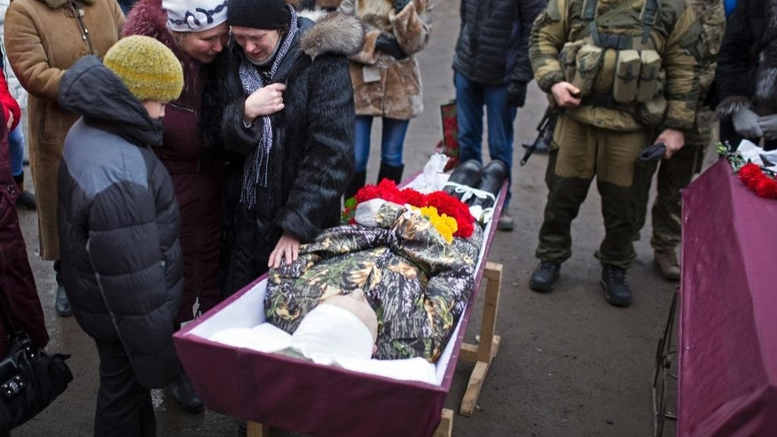 Relatives of a pro-Russian rebel fighter killed during fighting against Ukrainian government forces, mourn during his funeral in Vuhlehirsk, Donetsk region, eastern Ukraine, Thursday, Feb. 5, 2015, after the separatists recently burst through government lines in Vuhlehirsk.  The rebels are reported to have closed in around the town in a strategy they triumphantly refer to as the Debaltseve cauldron. (AP Photo/Vadim Braydov)